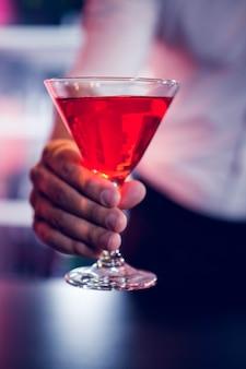 Barman die een rode martini in bar dienen