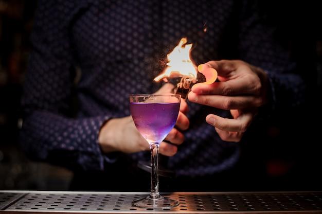 Barman die een sterke frisse paarse zomercocktail maakt met een rooknoot
