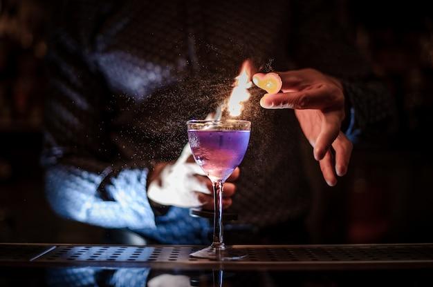 Barman die een sterke paarse zomercocktail met een rooknoot maakt