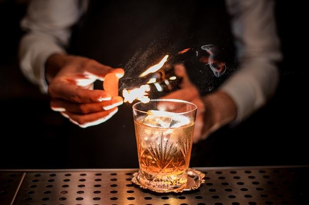 Barman die een verse en smakelijke ouderwetse de zomercocktail met sinaasappelschil en rooknota maken