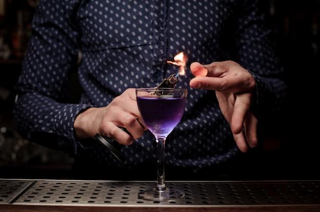 Barman die een zoete en verse paarse zomercocktail met een rooknoot maakt