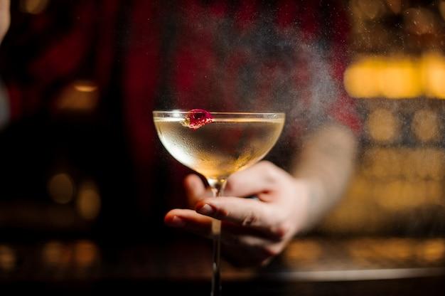 Barman die elegant cocktailglas met alcoholische drank houdt