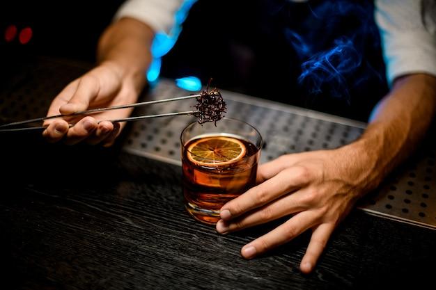Barman die gekoelde smeltende karamel met twezzers aan de cocktail toevoegen met gedroogde sinaasappel onder blauw licht en rook