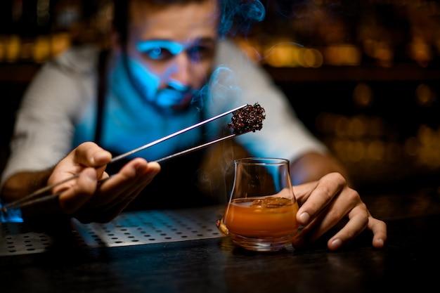 Barman die gekoelde smeltende karamel met twezzers toevoegen aan de cocktail met ijsblokjes onder blauw licht