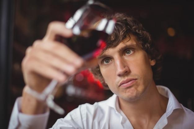Barman die glas rode wijn bekijkt