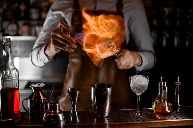 Barman die het grote ijsblokje op een pincet boven de stalen shaker in brand steekt
