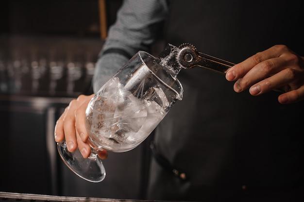 Barman die ijsblokjes in het cocktailglas zetten