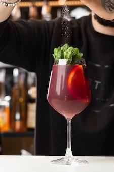 Barman die red sangria maakt in de italiaanse restaurant sangria-cocktail met rode wijn op de bar wazig