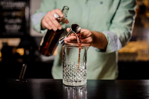 Barman die rode alcoholische cocktail, metaaljigger en baromgeving maakt