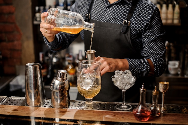 Barman die siroop in het grote cocktailglas gieten