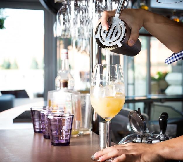 Barman die stalen schudbeker omhoog houden en gemengde drank in het glas met cocktail gieten.