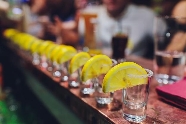Barman die sterke alcoholische drank in kleine glazen op bar gieten, schoten.