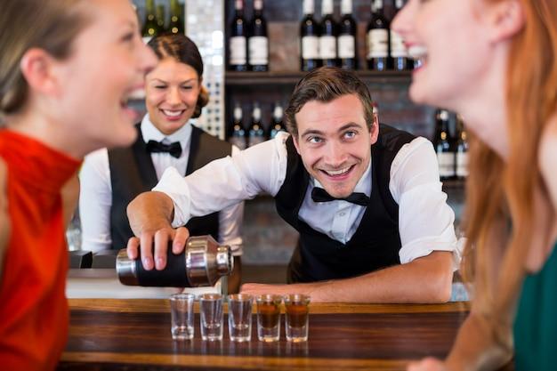 Barman die tequila giet in geschotene glazen