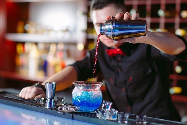 Barman die verse cocktail in buitensporig glas gieten