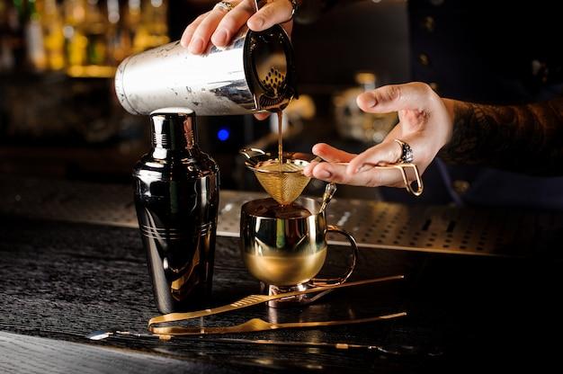 Barman die verse en smakelijke de zomerdrank in de kopermok gieten