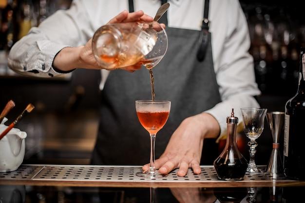 Barman die verse zoete alcoholische drank in het cocktailglas gieten