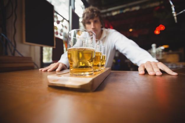 Barman die zich dichtbij teller met glazen bier bevindt