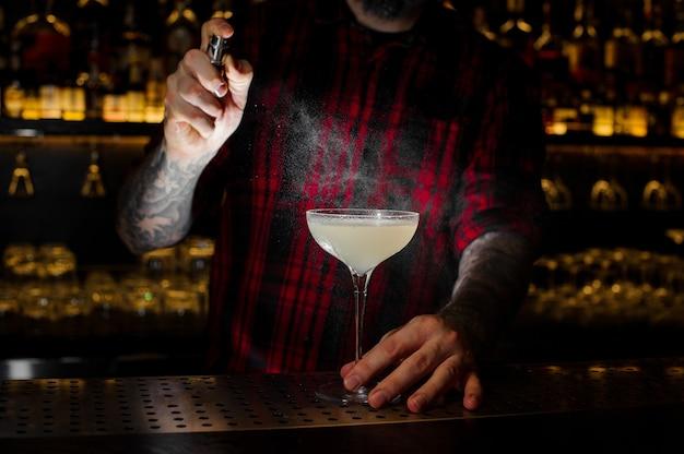 Barman elegante cocktailglas besprenkeld met lichte en smakelijke alcoholische drank met bitter op de bar