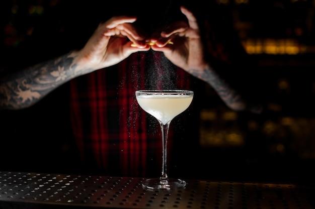 Barman elegante cocktailglas besprenkelen met lichte en smakelijke alcoholische drank met sinaasappelschil sap op de balk in het donker