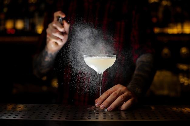 Barman elegante cocktailglas met lichte en smakelijke alcoholische drank met bitter beregening op de balk in het donker