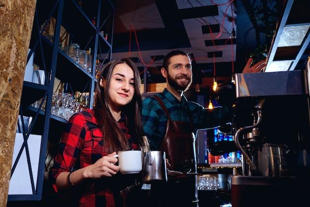 Barman en ober werken achter de toonbank in de bar
