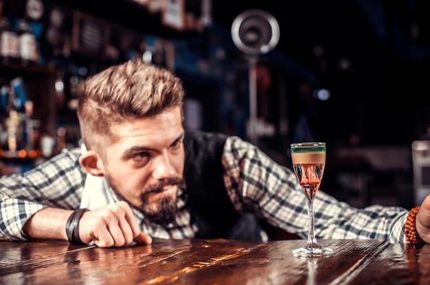 Barman formuleert een cocktail achter de bar