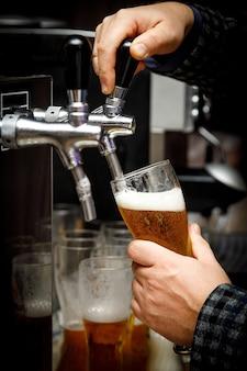 Barman giet bier in een glas.