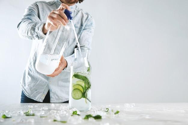 Barman giet bruisend water in vintage fles met ijs, komkommer en munt uit siphone om koude zomer gezonde drank zoals mojito zonder alcohol te maken