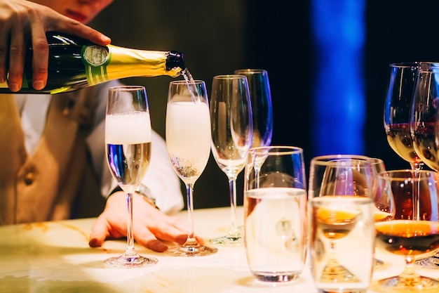 Barman giet champagne. ober gieten champagne op een feestje.