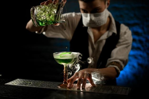Barman giet cocktail in glas wit medisch masker op zijn gezicht