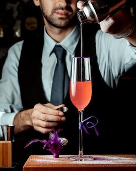 Barman giet cocktail van cocktailshaker