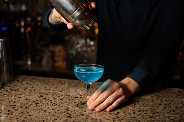 Barman giet de laatste druppels van de alcoholische cocktail blue lagoon van de shaker