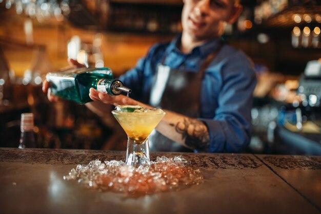 Barman giet drank in het glas met ijs