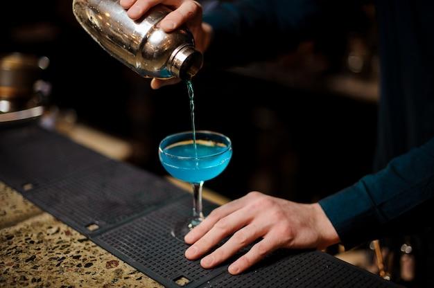 Barman giet een blue lagoon-cocktail met alcohol in het glas