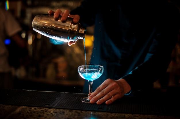 Barman giet van een shaker in een glas alcoholcocktail blue lagoon