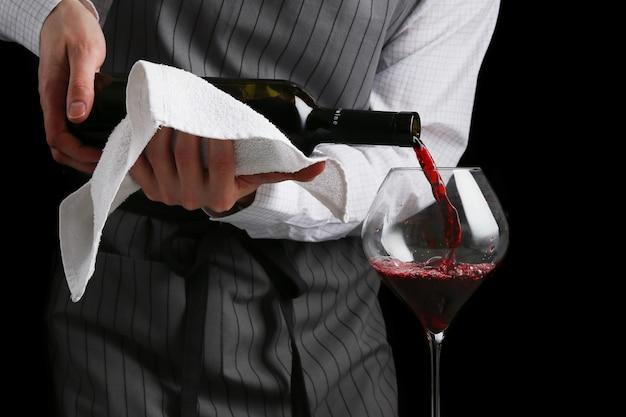 Barman giet wijn in glas op donkere achtergrond