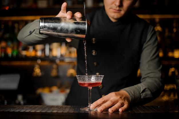 Barman gieten alcoholische drank met campari in het cocktailglas