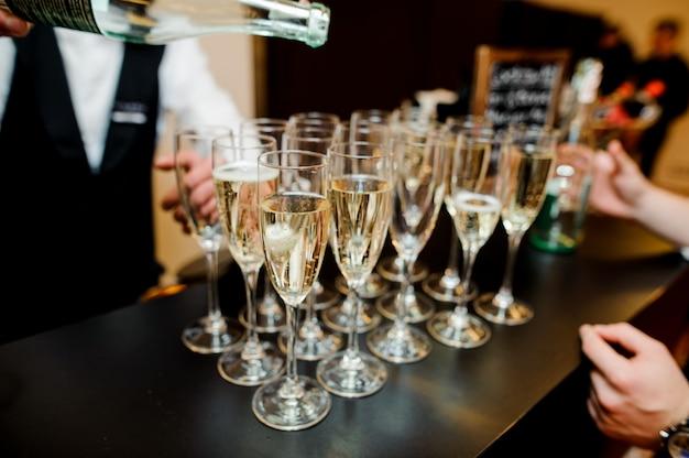 Barman gieten champagne in glazen op de bar