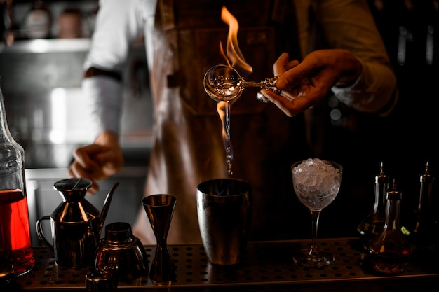 Barman gieten een essentie van de lepel in de vlam naar de stalen shaker