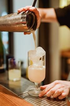 Barman gieten een pina colada drankje uit een shaker in een cocktailglas. foto met ondiepe scherptediepte. verticaal levensstijlbeeld.