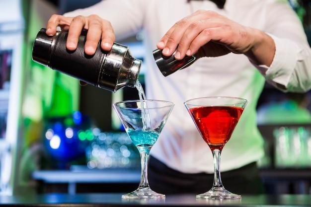 Barman gietende cocktail van schudbeker in glazen bij barteller in bar