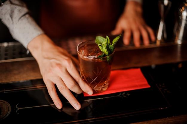 Barman houdt een cocktail met munt in zijn hand. geen gezicht