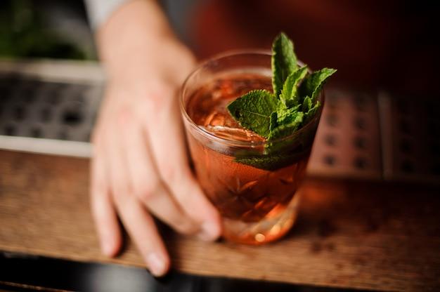 Barman houdt een cocktail met munt in zijn hand