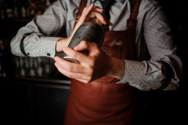 Barman in bruine schort die de schudbeker schudt