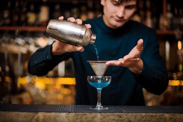 Barman in een blauw shirt filtert een blue lagoon-cocktail met alcohol