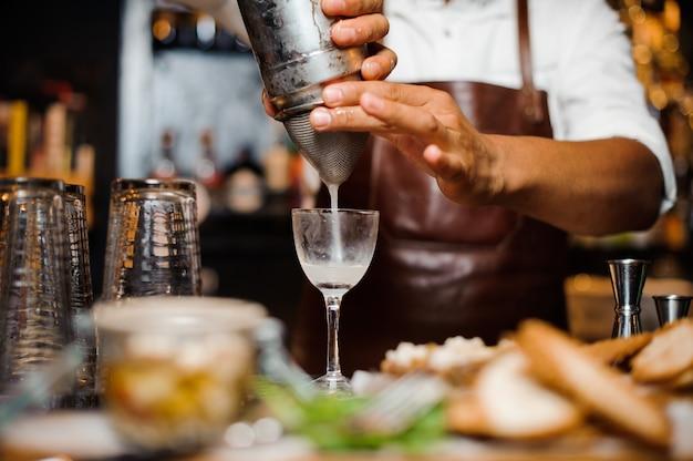 Barman in een bruin lederen schort gieten cocktail in het glas