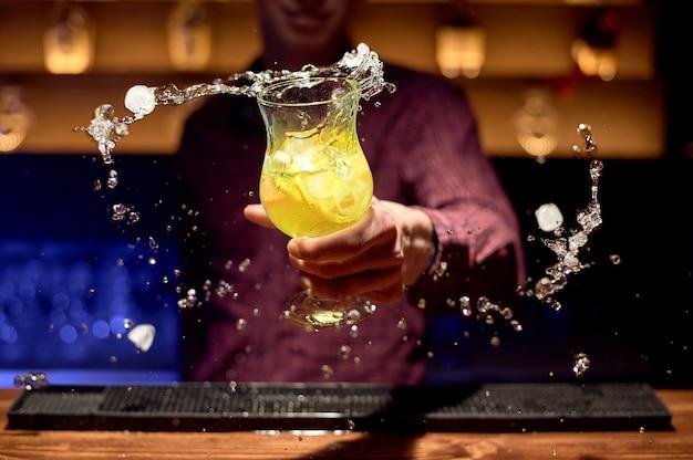 Barman in een nachtclub houdt een glas cocktail met spatten aan de zijkanten