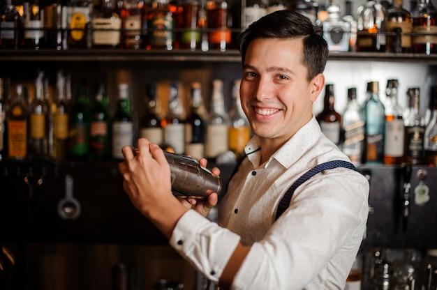 Barman in shirt maakt alcohol coctail geen gezicht van dichtbij