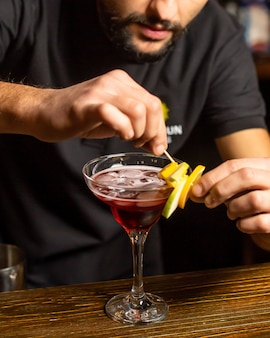 Barman ingericht cocktailglas met stukjes fruit op bamboespies