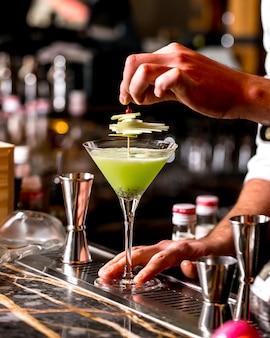 Barman ingerichte kiwi cocktail met appelschijfjes op bamboe spies